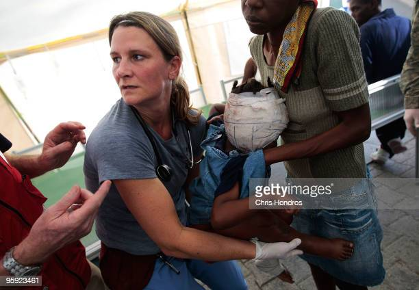 A doctor helps transfer a seriously wounded Haitian girl to a gurney for airlifting to the hospital ship USS Comfort January 21 2010 at the central...