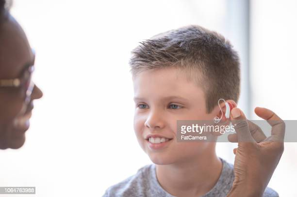 Doctor helps young boy with hearing aid