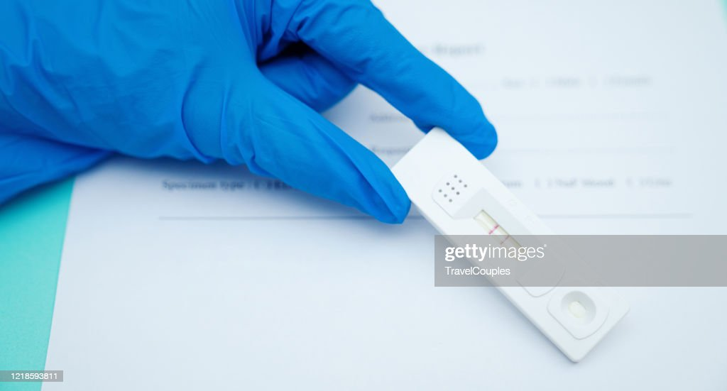 Doctor holding a test kit for viral disease COVID-19 2019-nCoV. Lab card kit test for viral novel coronavirus sars-cov-2 virus. Negative test result by using rapid test device for COVID-19 : Stock Photo