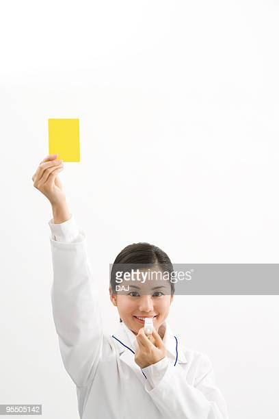 doctor holding a yellow card - 笛 ストックフォトと画像