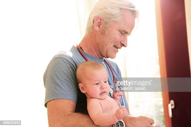 doctor holding baby - sigrid gombert stock pictures, royalty-free photos & images