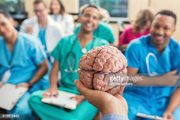 Doctor holding brain model during a health care seminar