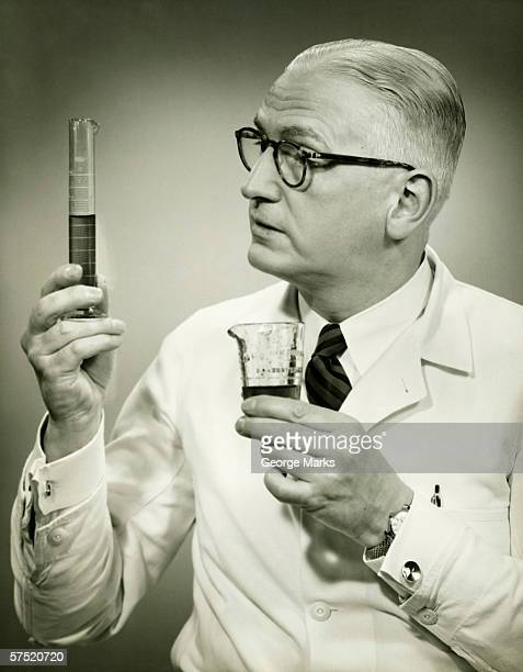 Doctor holding buretts in studio, (B&W), portrait