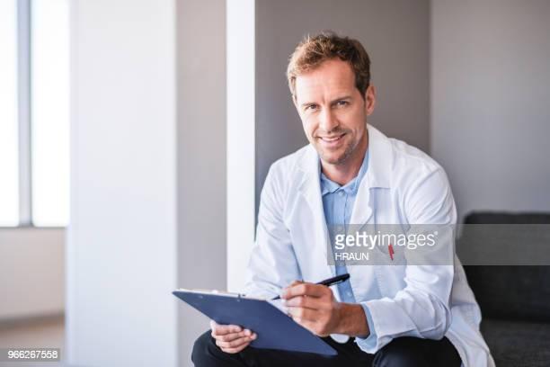 médico sosteniendo portapapeles y pluma en hospital - bata de laboratorio fotografías e imágenes de stock