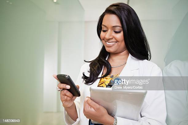 Doctor holding digital tablet and cell phone
