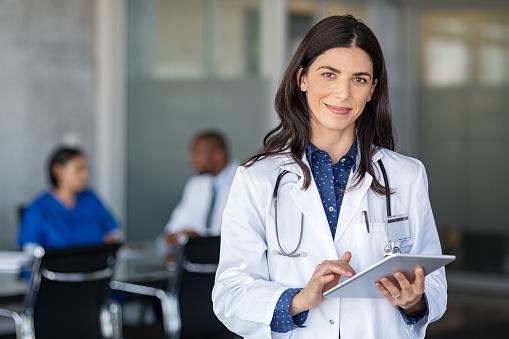Doctor holding digital tablet at meeting room 1189304032