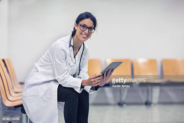 Doctor holding digital tablet in waiting room