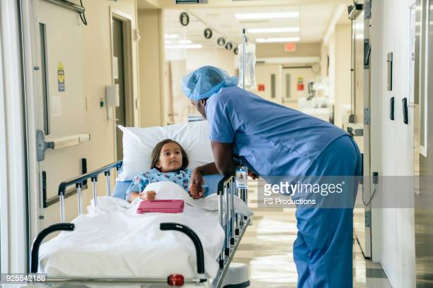 doctor holding hand of girl in hospital gurney - girl in hospital bed sick stock photos and pictures