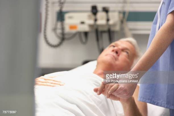 Doctor holding male patient's hand in hospital room