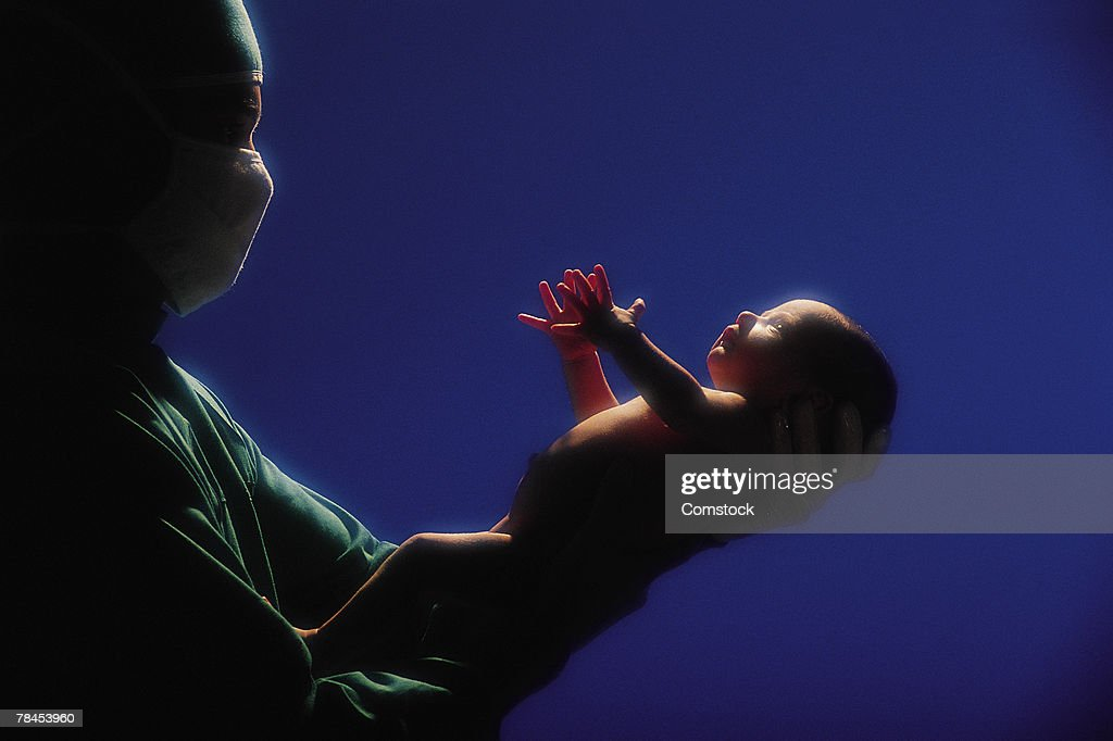 Doctor holding newborn baby : Stock Photo