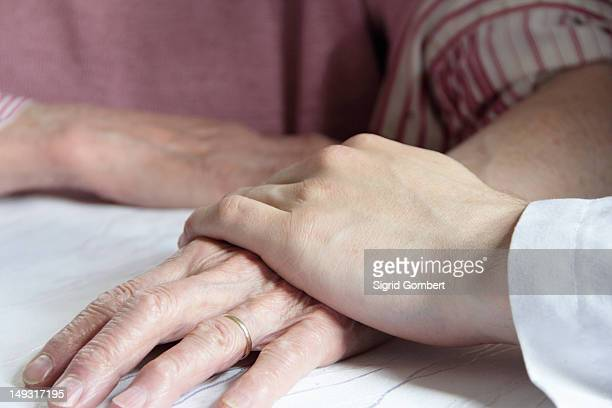 doctor holding older womans hand - sigrid gombert stock pictures, royalty-free photos & images