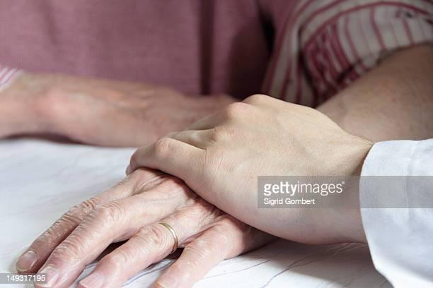 doctor holding older womans hand - sigrid gombert - fotografias e filmes do acervo