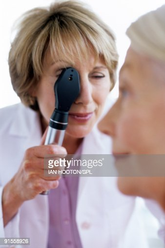Doctor Holding Ophthalmoscope Checking Womans Eye High Res