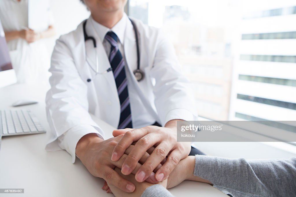 Doctor holding patient hand to give a support : Stock Photo