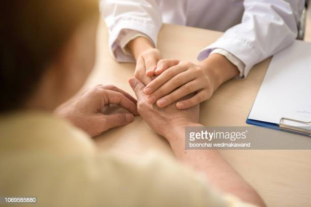 doctor holding patient's hand, helping hand concept - patient safety stock pictures, royalty-free photos & images