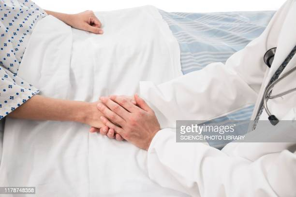 doctor holding patient's hand - hospice stock pictures, royalty-free photos & images