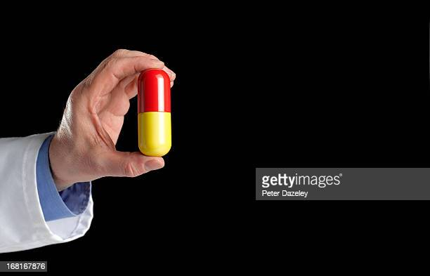 Doctor holding pill