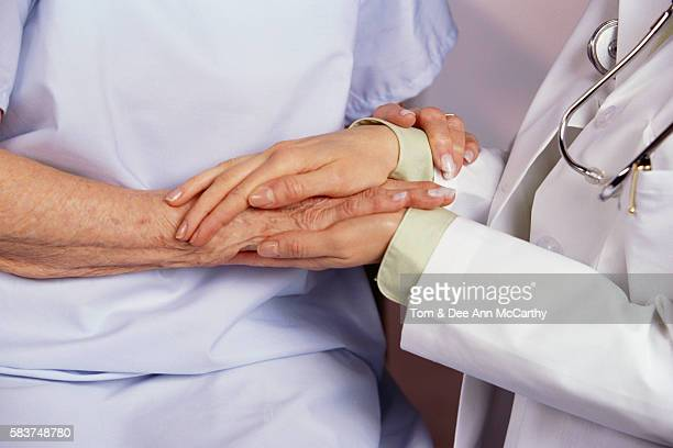 doctor holding senior patient's hand - gerontology stock pictures, royalty-free photos & images