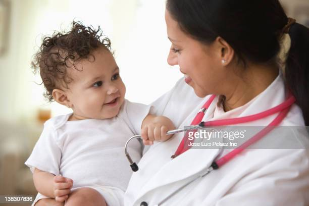 Doctor holding smiling baby girl