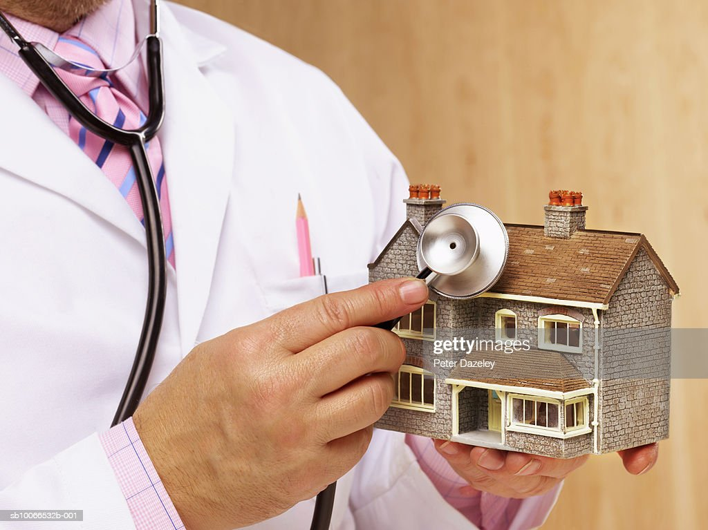 Doctor holding stethoscope to model house, mid section : Stock Photo