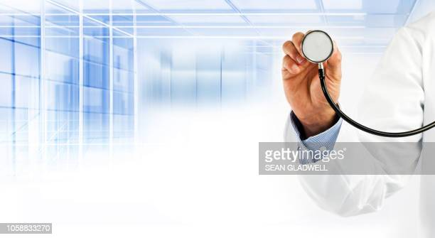 doctor holding stethoscope wearing white coat - stethoscope stock pictures, royalty-free photos & images