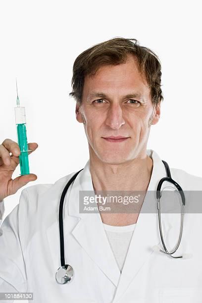 A doctor holding up a syringe