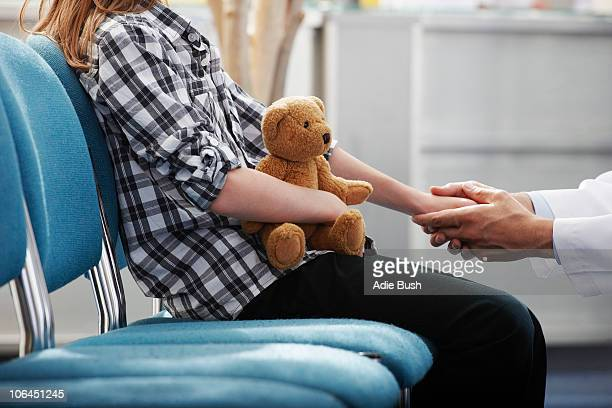 Doctor holding young girls hand