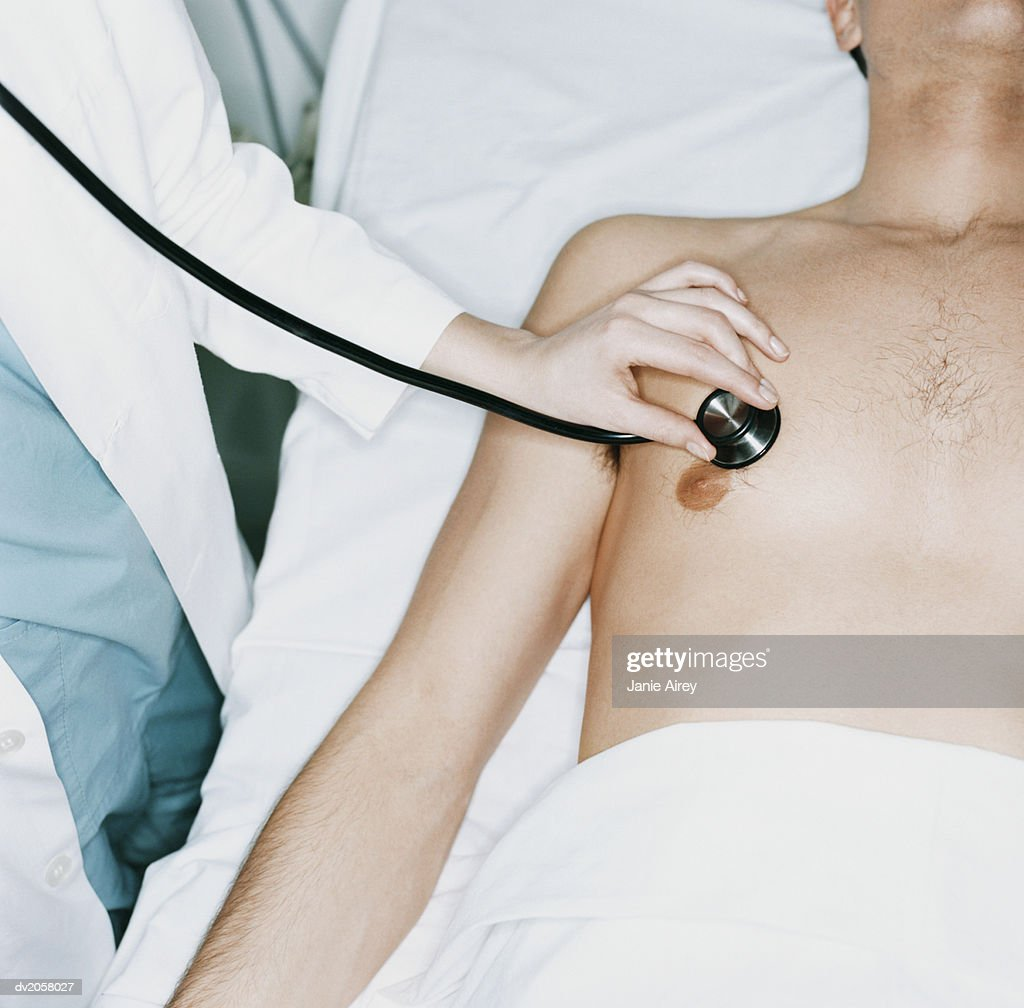 Doctor Holds a Stethoscope to a Male Hospital Patient's Chest : Stock Photo