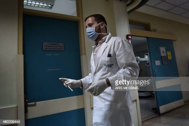 A doctor holds a syringe as he walks in the corridor of an Athens hospital on July 8 2015 With expectations of a Greek exit from the eurozone...