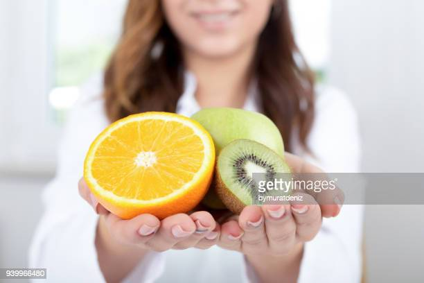 doctor holds some fruits - nutritionist stock pictures, royalty-free photos & images