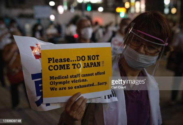 Doctor holds up a poster asking people not to come to Japan for the Olympics during a protest against the Olympic Games on June 23, 2021 in Tokyo,...