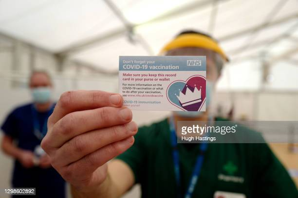 Doctor holds up vaccination card as over eighties receive their Covid-19 vaccinations on January 26, 2021 at Stithians Showground, near Truro,...