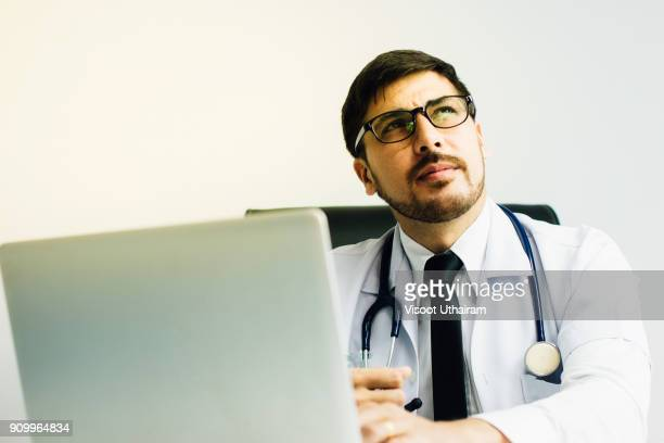 Doctor in a lab coat holding a stethoscope.