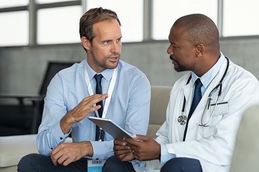 Doctor in conversation with pharmaceutical representative 1189303727