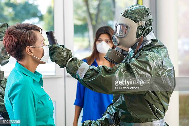 doctor in hazmat suit examining woman during contagious outbreak - plague stock photos and pictures
