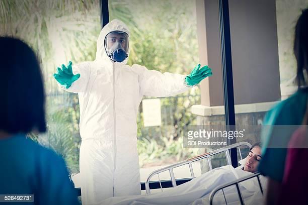 Arzt in hazmat passende Warnung Krankenschwestern in der Nähe von infizierten Patienten
