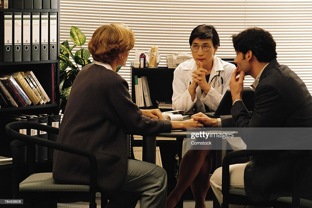 Doctor in her office talking to couple : Stockfoto