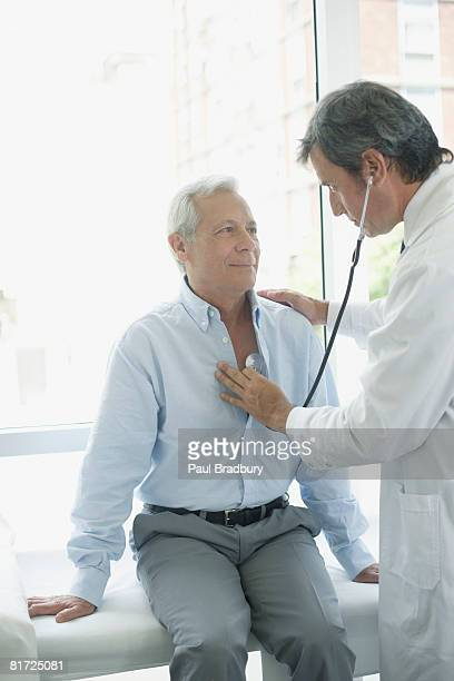 Doctor in hospital room with patient using stethoscope