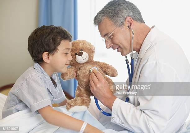 Doctor in hospital using stethoscope on young patient's teddy bear