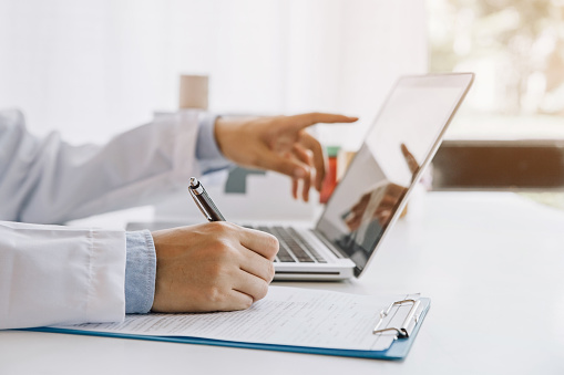 Doctor in hospital writing medical documentation and using laptop 1156853489