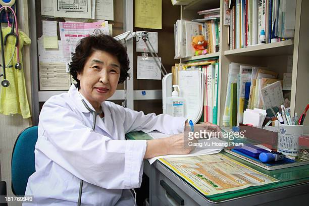 Doctor in Kyoto. She is sitting by her desk in her clinic. June 2013, Kyoto, Japan.