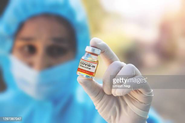 a doctor in medical gloves and mask holding an coronavirus vaccine. coronavirus, epidemic and medicine concept. - india stock pictures, royalty-free photos & images