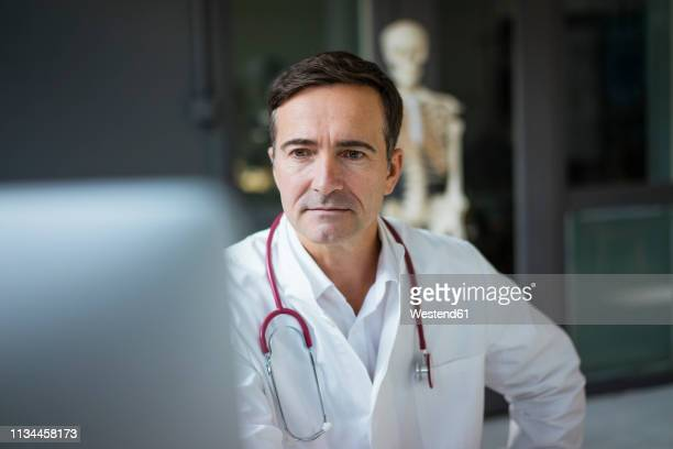 Doctor in medical practice looking at computer with skeleton in background