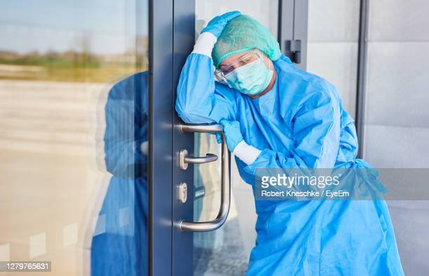 doctor in protective clothing takes a break because of stress and exhaustion from coronavirus - one mature woman only stock pictures, royalty-free photos & images