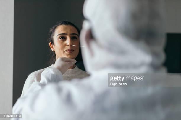 arzt in schutzarbeitskleidung unter nasenabstrich test von jungen frau - wissenschaftliches experiment stock-fotos und bilder