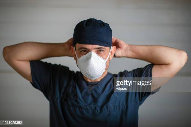 doctor in scrubs and face mask portrait during lockdown fastening mask looking at camera - essential workers stock pictures, royalty-free photos & images