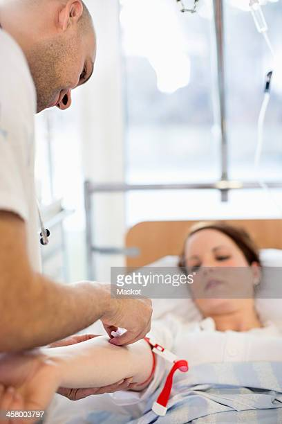 Doctor injecting female patient on bed in clinic