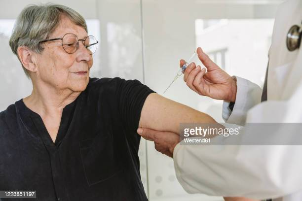 doctor injecting vaccine into senior patient?s arm - medical injection stock pictures, royalty-free photos & images