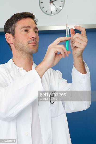 Doctor inspecting injection