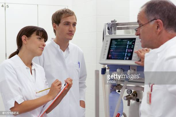 Doctor instructing younger man and woman
